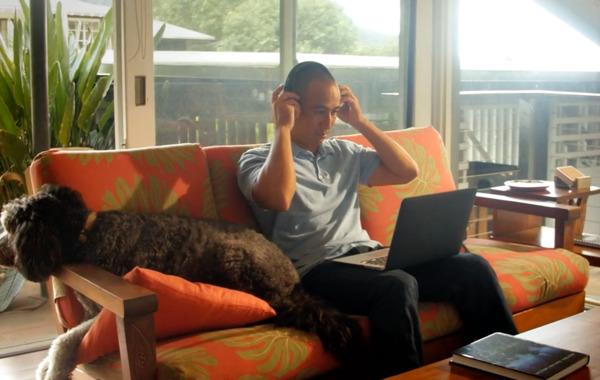 A distance learning executive MBA student is studying on his couch alongside his dog.