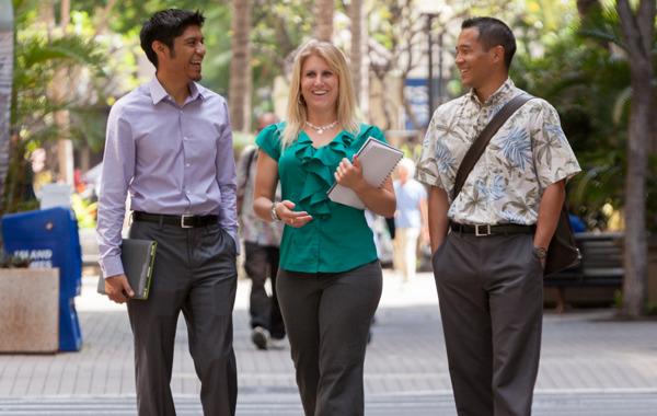 Three Shidler graduate students walking downtown.