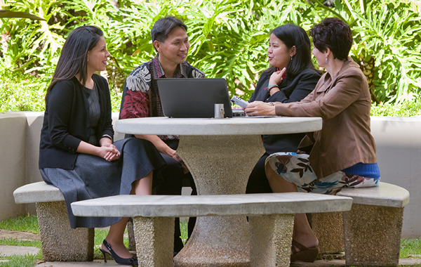 Four students work on a group project in the Shidler courtyard.