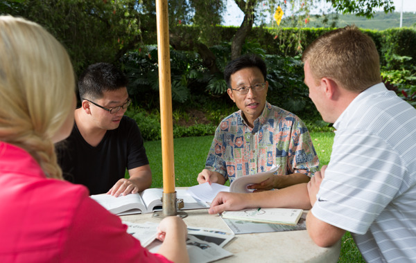 PhD students meet with Professor Victor Huang at a table.
