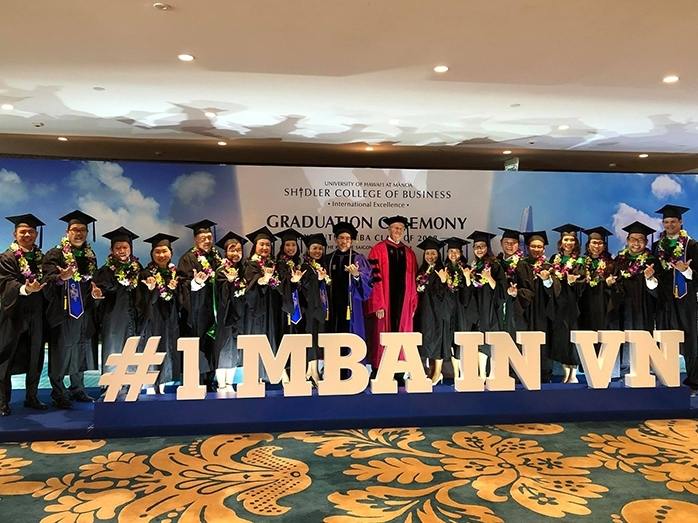 Shidler Professor and VEMBA Director Tung Bui and Shidler Dean Vance Roley (center) celebrate with the VEMBA class at a commencement ceremony in Ho Chi Minh City.